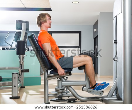 Hip abduction blond man exercise at gym indoor closing legs workout - stock photo