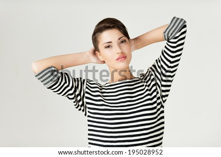 Hip and striped. Fashionable young short hair woman in striped clothing keeping arms crossed and looking at camera - stock photo