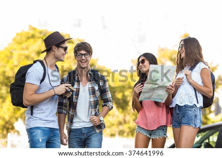 Hip friends checking map during a trip - stock photo