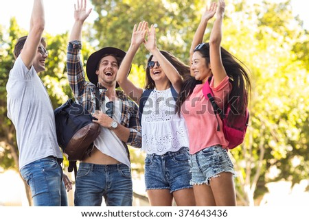 Hip friends cheering up with arms raised in the streets - stock photo