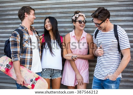 Hip friends looking at smartphone and leaning against rolling door