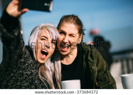 Hip girls taking a selfie in cafe