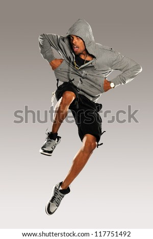 Hip Hop Dancer jumping wearing shorts and tennis shoes on a neutral background