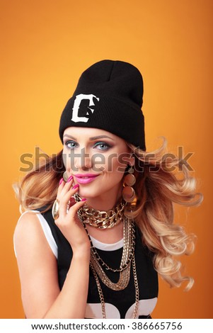 Hip-hop woman in cap with long  hair. Fashion portrait of modern girl in cap. - stock photo