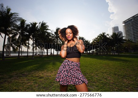 Hip trendy woman posing in the park - stock photo