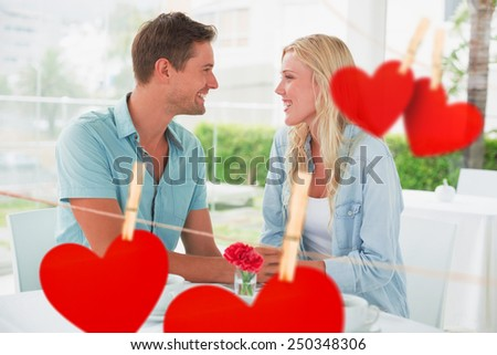 Hip young couple having desert and coffee together against hearts hanging on a line - stock photo