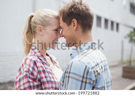 Hip young couple hugging and facing each other on a sunny day in the city - stock photo