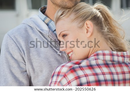 Hip young couple hugging each other on a sunny day in the city - stock photo