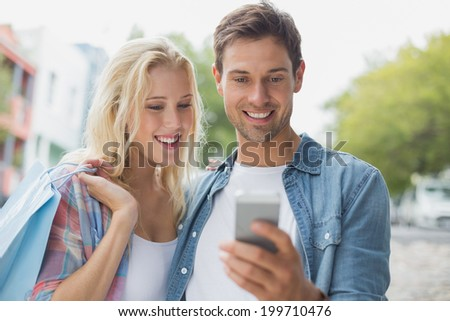 Hip young couple looking at smartphone on shopping trip on a sunny day in the city - stock photo