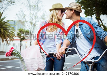 Hip young couple on a bike ride against heart - stock photo