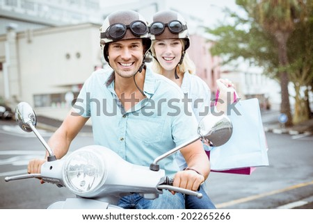 Hip young couple riding scooter with shopping bags on a sunny day in the city