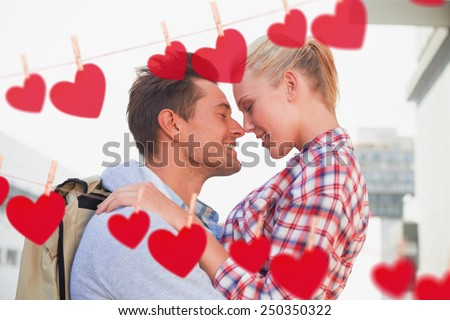 Hip young couple smiling at each other against hearts hanging on a line - stock photo