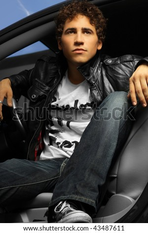 Hip young man in a car wearing leather jacket - stock photo
