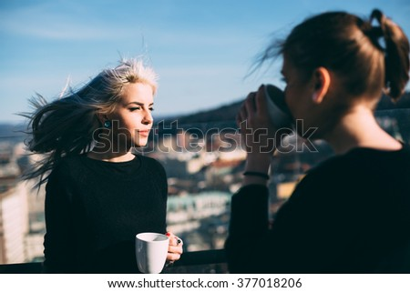 Hip young womendrinking coffee in roof top cafe - stock photo