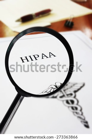 HIPAA healthcare document with magnifying glass                                - stock photo
