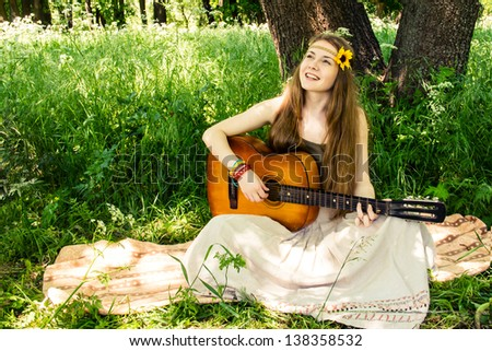 Hippie ethnic smiling girl singer with guitar in the forest - stock photo