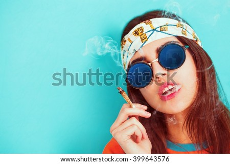 Hippie girl portrait smoking and wearing sunglasses - stock photo