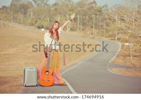 Hippie girl with guitar hitchhiking on countryside road