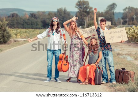 Hippie Group Hitchhiking on a Countryside Road - stock photo