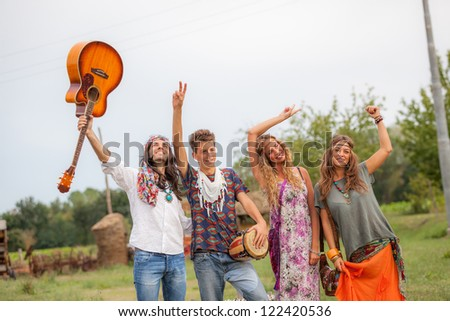 Hippie Group Playing Music and Dancing Outside - stock photo