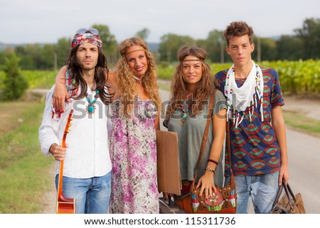 Hippie Group Walking on a Countryside Road - stock photo