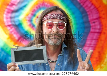 Hippie peaceful middle-aged man making victory sign while showing a small blank rectangular old blackboard, portrait on bright colorful background