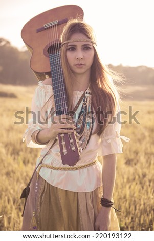 Hippie woman walking in golden field with acoustic guitar - stock photo