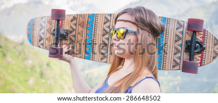 Hippie young and beautiful girl with skateboard longboard,  outdoor at mountain. She has a bandage on his forehead. Letterbox format design for website or banner
