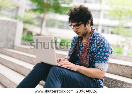 Hipster blogging while sitting on the steps outdoors - stock photo