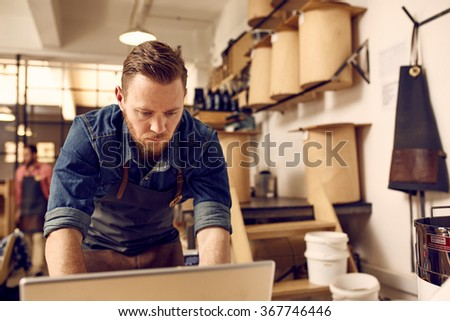 Hipster business owner working on laptop in his modern work  - stock photo