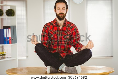 Hipster businessman meditating at his desk in his office - stock photo