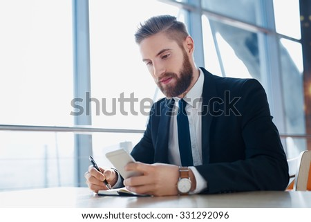 Hipster businessman taking notes from smartphone at modern office - stock photo