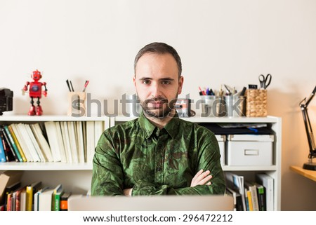 Hipster businessman using laptop in his office. - stock photo