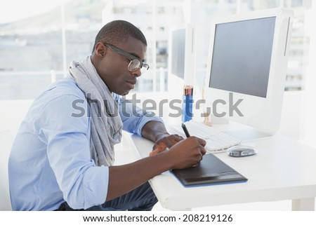 Hipster businessman working at his desk in his office