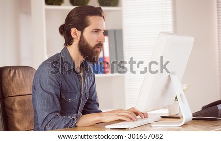 Hipster businessman working at his desk in his office - stock photo