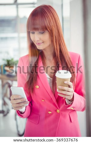 Hipster businesswoman holding coffee cup and smartphone in office - stock photo