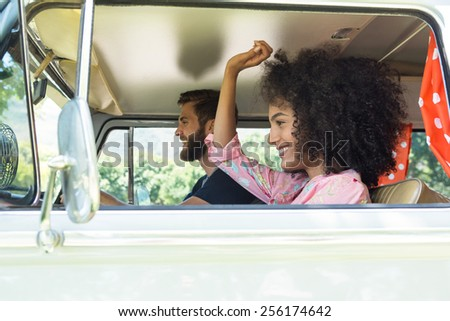 Hipster couple driving in camper van on a summers day - stock photo