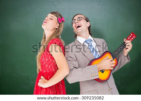 Hipster couple having fun together against green chalkboard