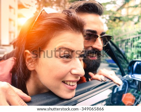 Hipster couple looking outside from their cabrio having fun together - Love and travel concept - Warm light filtered look with sunshine halo - stock photo