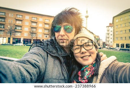 Hipster couple of tourists taking a selfie in Berlin City - Multiracial concept of friendship and fun with new trends and technology - Asian girl with alternative young fashion handsome guy  - stock photo