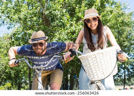 Hipster couple on a bike ride in the park on a summers day - stock photo