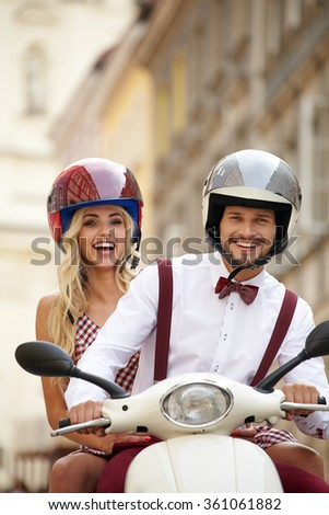 Hipster  couple riding a scooter on a sunny day in the city