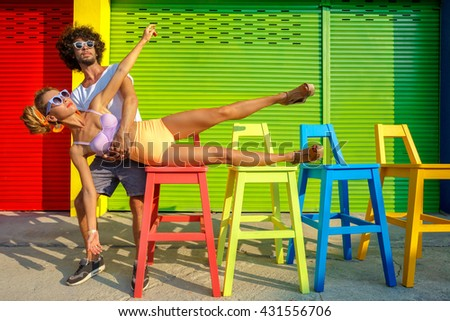 Hipster couple wearing stylish bright outfits and glasses, going crazy and having great time together.