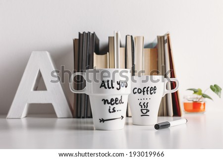 Hipster cup of coffee on a books library./ Two white coffee mug with diy decoration.  - stock photo