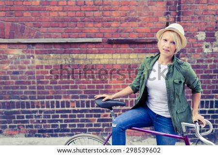 Hipster cyclist young beautiful girl with vintage road bike on city street, urban scene. Commuting to work concept. Woman cycling on fixed gear bike in town, retro city street industrial background. - stock photo