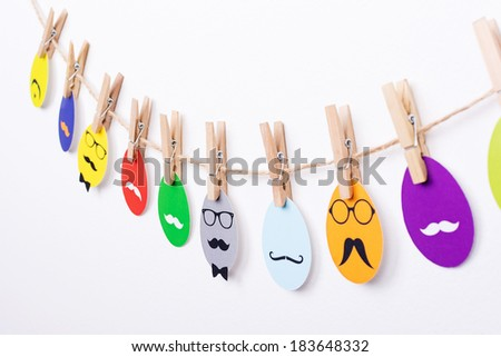 Hipster Easter printed eggs hanging on a rope with clothespin. Easter eggs colorful printed decoration on the white wall. - stock photo