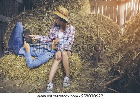 Hipster farming couple with laptop computer in the barn against hay background.