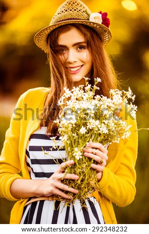 Hipster fashion girl in straw hat keep beauty flowers on hands