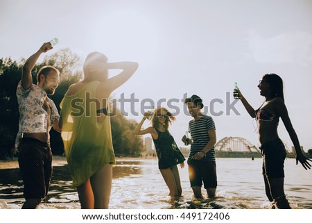 Hipster Friends Dancing At River Shallow And Having Fun