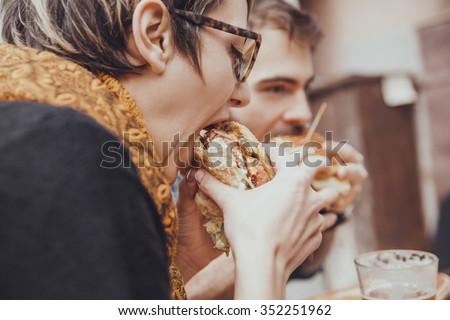 Hipster Friends In Fast Food Reastaurant Eating Burgers - stock photo